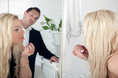 Man watching a beautiful woman. Reflection in a large mirror of a men watching a beautiful blond women apply her makeup putting lipstick on her lips with an Royalty Free Stock Photo