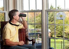 Man watching bird on feeder Stock Photos