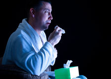 Man watching chick flick. Crying  Caucasian man with a tissue watching a movie on television Stock Image