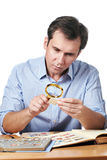 Man watching a collection of postage stamps Royalty Free Stock Images