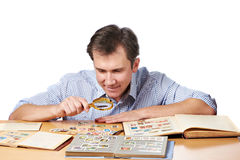 Man watching a collection of postage stamps with magnifier Stock Images