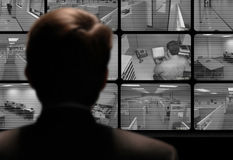 Man watching employee work via closed-circuit video monitor