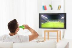 Man watching football and drinking beer at home Royalty Free Stock Photos