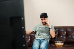 Man watching football, football fan, sports at home. stock photos
