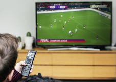 Man watching a football game on TV Stock Photo