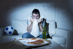 Man watching football game on tv nervous and excited suffering stress on couch Royalty Free Stock Photo
