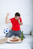 Man watching football game on tv in team jersey celebrating goal crazy happy jumping on sofa Stock Photos