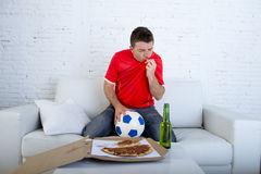 Man watching football game on tv in team jersey celebrating goal crazy happy jumping on sofa Royalty Free Stock Photography