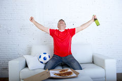 Man watching football game on tv in team jersey celebrating goal crazy happy jumping on sofa Royalty Free Stock Photos