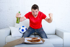 Man watching football game on tv in team jersey celebrating goal crazy happy jumping on sofa Stock Photo