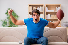 The man watching football at home sitting in couch Stock Photos