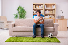 The man watching football at home sitting in couch Stock Image