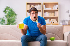 The man watching football at home sitting in couch Stock Images