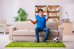 The man watching football at home sitting in couch Stock Photo