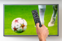 Man is watching football match on TV. And holding tv remote controller in hand Stock Photo
