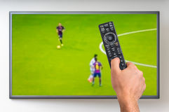 Man is watching football match on TV. And holding tv remote controller in hand Stock Photos