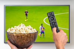 Man is watching football match on TV. And holding tv remote controller and popcorn in hands Stock Images