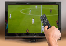 Man is watching football match on TV. And holds remote controller in hand Stock Photography