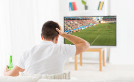 Man watching football or soccer game on tv at home Royalty Free Stock Photo
