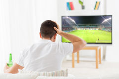Man watching football or soccer game on tv at home Stock Photo