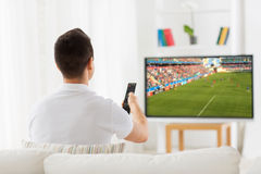 Man watching football or soccer game on tv at home Stock Photography