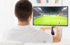Man watching football or soccer game on tv at home Stock Image