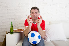 Man watching football on tv nervous and excited suffering stress crossing fingers for goal Stock Photography