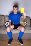 Man watching football on tv and showing yellow car. Young attractive man watching football on tv at home and showing yellow card Royalty Free Stock Images