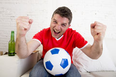Man watching football on tv wearing team jersey celebrating goal happy on sofa. Young fan man watching football game on television wearing team jersey Stock Photography