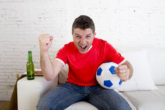 Man watching football on tv wearing team jersey celebrating goal happy on sofa. Young fan man watching football game on television wearing team jersey Royalty Free Stock Photo
