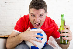 Man watching football on tv wearing team jersey celebrating goal happy on sofa Royalty Free Stock Images