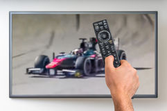 Man is watching formula one racing on TV Stock Images