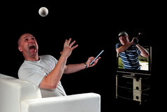 Man watching golf on 3D television. Man surprised at realistic image of golf ball and golfer coming out of 3D TV Royalty Free Stock Photo