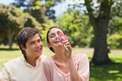 Man watching his friend while she is smelling a flower Stock Image
