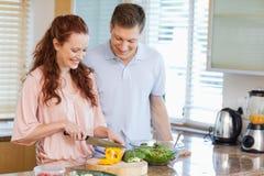 Man watching his girlfriend preparing a salad Stock Photography