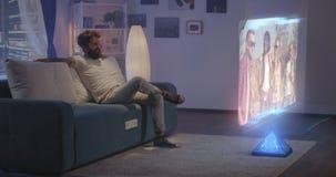 Man watching holographic TV at night