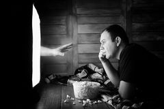 Watching a horror on TV black and white. A man watching a horror movie on TV black and whiter Stock Photo