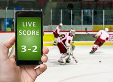 Man is watching ice hockey and holds smartphone in hand with live score Royalty Free Stock Photography