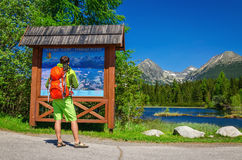 Man watching map of mountain trails by lake Stock Image