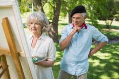 Man watching mature woman paint in park Stock Photos