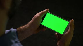 Man watching media content on a smart phone with green screen stock video