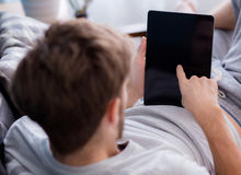 Man watching media content in a tablet sitting on a couch. Happy man watching media content in a tablet sitting on a couch at home, Top side view mock up Stock Image