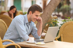 Man watching media in a laptop in a restaurant Stock Image