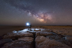 Man watching the Milky Way Galaxy rise from a Jetty. A man triggers his light sphere to explore the rocks under the Milky Way galaxy Royalty Free Stock Photo