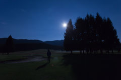 Man watching moon in golf course of Cansiglio Forest. Veneto, Italy Stock Photo