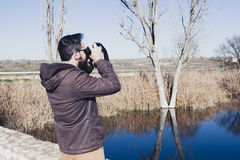Man watching nature with binoculars next to the river. Stock Photography