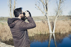 Man watching nature with binoculars next to the river. Royalty Free Stock Image