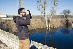 Man watching nature with binoculars nexto to the river. Stock Images