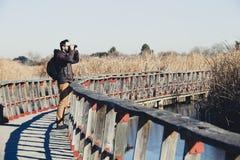 Man watching nature with binoculars, in a wood bridge Stock Photos