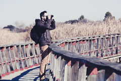 Man watching nature with binoculars, in a wood bridge over the w Royalty Free Stock Images